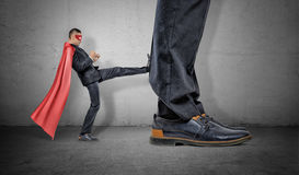 A tiny businessman in a red cape and an eyemask kicking at a retreating giant foot. Market players. Small and big companies. Workplace competition Royalty Free Stock Photography
