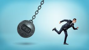 A tiny businessman runs away from a large iron ball with a word DEBT swinging on a chain. Debt return. Financial trouble. Debt collection Stock Photos