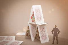Tiny businessman standing near house of cards