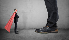 A tiny businessman in a superhero cape stands facing giant man with only his feet seen. Stock Image