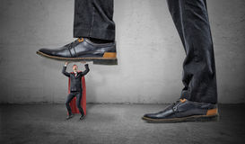 A tiny businessman in superhero red cape trying to hold a giant boot stepping on him. royalty free stock photos