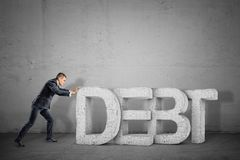 A tiny businessman trying hard to move giant concrete letters forming a word DEBT. royalty free stock images