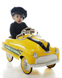 Tiny Cabbie. A toddler cab driver wering a cabbie hat and driving a yellow pedal-car taxi.  On a white background Royalty Free Stock Image
