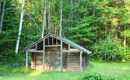 Tiny Cabin. Tiny log cabin in a grassy clearing Royalty Free Stock Image