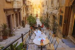 Tiny cafes with tables on stairs of narrow street,Valletta, Malta royalty free stock image