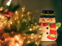 Ceramic Snowman and Christmas Decorations. A tiny ceramic snowman suited up with a scarf and black top hat is standing with a smile on his face and arms open Royalty Free Stock Photo