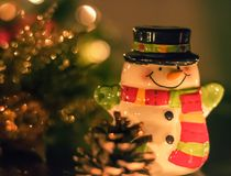 Ceramic Snowman Christmas and Decorations. A tiny ceramic snowman suited up with a scarf and black top hat is standing with a smile on his face and arms wide Royalty Free Stock Photos