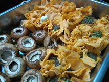 Paprika infused tartlets with tangy goat& x27;s cheese in a tray. Tiny cheshunt mushrooms Stock Images