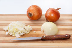 Tiny chopped onions on a kitchen wooden board Stock Image