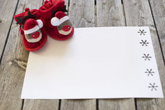 Tiny christmas slippers on boards with white paper Royalty Free Stock Photos