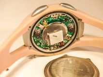 Intricate Electronics in a Watch. The tiny circuit board containing numerous intricate pieces to create a working watch stock photography