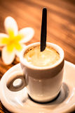 Tiny cup coffee with yellow frangipani flower Royalty Free Stock Image
