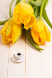 Tiny cup of coffee and yellow tulips Stock Photo