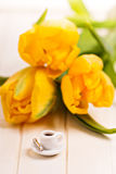 Tiny cup of coffee and yellow tulips Stock Photos