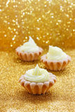 Tiny cupcakes on golden background Royalty Free Stock Image