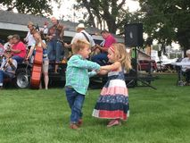 Tiny dancers. Two young children have fun at a local park dancing to the band Royalty Free Stock Photo