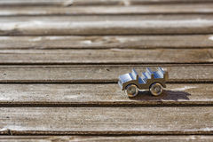 Tiny die cast metal toy car on wooden deck. Close up on tiny die cast metal toy open top car on sunny wooden deck with copy space royalty free stock photography