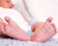 Tiny Feet. View of newborn from the bottom of his feet.  Shallow depth of field with focus on the feet Stock Photo