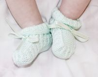 Tiny feet of baby in a bootees Stock Photo