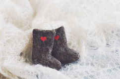 Tiny felted valenki with hearts on knitted downy shawl Stock Photography