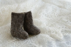 Tiny felted valenki on knitted downy shawl Stock Photo