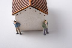 Tiny figurine of men in front of a house Royalty Free Stock Photography