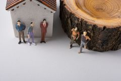 Tiny figurine of men in front of a house Royalty Free Stock Photos