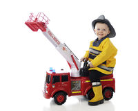 Tiny Fire Fighter. An adorable toddler happily playing fireman on his toy fire truck.  On a white background Royalty Free Stock Images