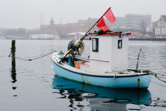 Tiny fishing boat - Sonderborg, Denmark. A one-person fishing boat lies towed in the small harbor of Sonderborg - blue hull, white steering house and red flags Stock Photography