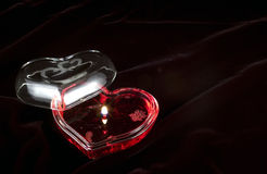 Tiny Flame of Romance. Romantic heart shaped gel candle with cover and tiny glowing flame isolated on black Royalty Free Stock Image