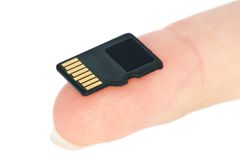 Tiny flash memory card on fingertip. Isolated on the white background Stock Images