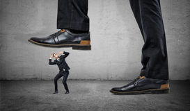 Tiny frightened businessman under feet of huge man. A tiny frightened man under a feet of a huge businessman on grey wall background. Chiefs pressure. Stress on Stock Photo