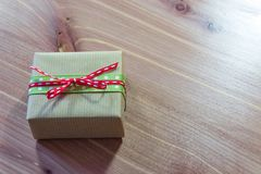 Tiny gift box wrapped in rustic brown kraft paper with red and green ribbons, simple bow Royalty Free Stock Images