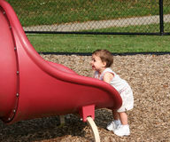 Tiny Girl Big Slide. Cute baby girl wanting to get on big red slide at park. Shot with a Canon 20D stock photos