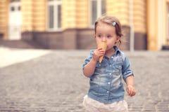 Tiny girl eating ice cream Royalty Free Stock Photos