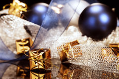 Tiny golden christmas present in front of christma. Tiny shiny golden christmas present in front of christmas decoration with christmas balls and ribbons Stock Image