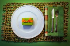 Tiny green gift box with orange ribbon on a white plate. With green and plaid napkins on a woven placemat background Royalty Free Stock Photography