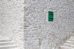 Stony white background with small green window. Tiny green window on white facade of renovated stone house royalty free stock photo