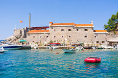 The tiny harbor. The old town of Petrovac with the ruins of the medieval fortress and small port for tourist and fishing boats, Montenegro Royalty Free Stock Images