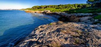 Tiny harbor with small sand beach in rocky seashore near Tarragona, Spain Royalty Free Stock Images