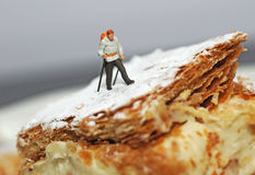 Tiny hiker. Small hiker figure walking on a piece of cake with castor sugar imitating snow Stock Photo