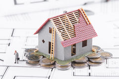 Tiny house stands on coins. The concept of banking, loans, expen Stock Photography