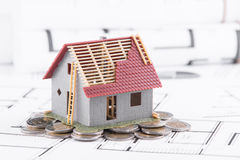 Tiny house stands on coins. The concept of banking, loans, expen Stock Image