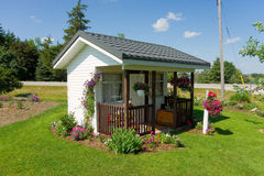 A tiny house surrounded by flowers Royalty Free Stock Photography