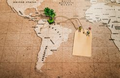 Tiny human models on price tag on world map with palm tree Royalty Free Stock Images