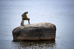 Tiny Inuksuk Atop Boulder in River. A small inuksuk (inuckshuk) sits on top of a lone boulder in surrounding water Stock Images