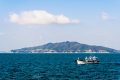 Tiny island and fisherman boat Royalty Free Stock Photos