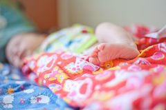 Tiny leg newborn baby in pink diapers Royalty Free Stock Photos