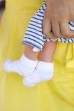 Tiny legs of newborn baby in white sokcs Stock Image