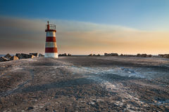 Tiny lighthouse at sunset royalty free stock photo